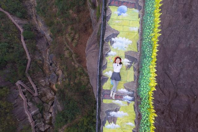 美女游客躺在石牛寨3D油菜花栈道